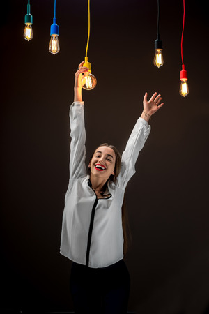 business ideas: Young creative girl hanging holding with hand illuminated retro lamp on the dark background. Creativity concept Stock Photo