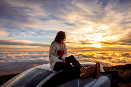 Young woman in sweater with heart shape enjoying beautiful cloudscape sitting on the car roof above the clouds on the sunrise