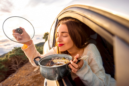 Young woman holding cooking pan with rice and fish looking out the car window on the roadside. Healthy travel eating concept Imagens - 54122821