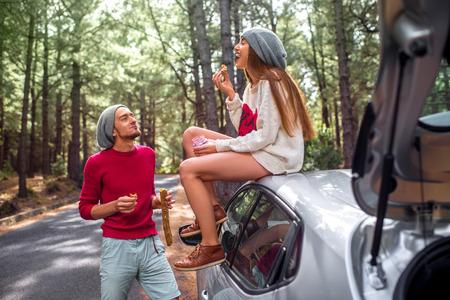 merienda: Pareja joven y hermosa en suéteres y sombreros que se divierten, comiendo baguette con mermelada cerca del coche en la carretera en el bosque de pinos. Familia joven que se bocadillo rápido mientras viaja
