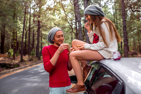 quick snack: Young and lovely couple in sweaters and hats having fun, eating baguette with jam near the car on the roadside in the pine forest. Young family having quick snack while traveling