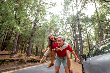 piggyback: Playful young couple in sweaters and hats having a piggyback ride near the car on the pine forest roadside. Wide angle image with copy space