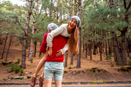 piggyback: Young playful couple in sweaters and hats having a piggyback ride in the pine forest. Stock Photo