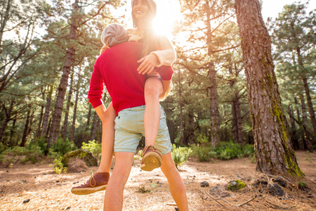 piggyback: Young playful couple in sweaters and hats having a piggyback ride in the pine forest. Strong cropped image composition Stock Photo