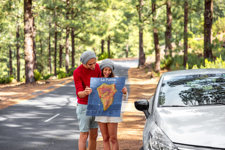 rented: Young family in sweaters and hats holding paper map traveling La Palma island by rented car in the forest