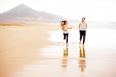 running pants: Young and lovely couple in white t-shirts and black pants running beautiful sandy beach with mountains on background on Fuerteventura island in Spain. General plan with copy space