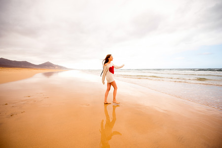 Young woman in sweater having fun enjoying beautiful sandy beach on the foggy weather on Fuerteventura island in Spain. General plan with a lot of space