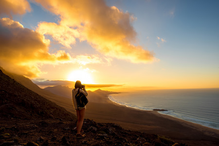 seascape: Beautiful seascape view on Cofete coastline with young female traveler on the sunset on Fuerteventura island in Spain. General plan with a lot of space Stock Photo