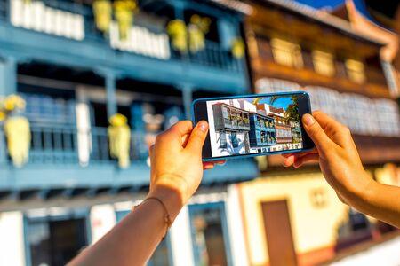 santa cruz: Female hands photographing with smart phone old colorful balconies in Santa Cruz de la Palma in Spain