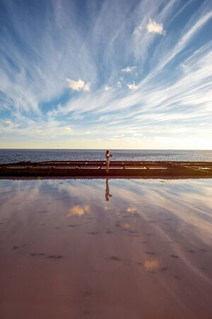 salt water: Volcanic pool with woman standing on the salt manufaturing with pink salt water and reflection on La Palma island