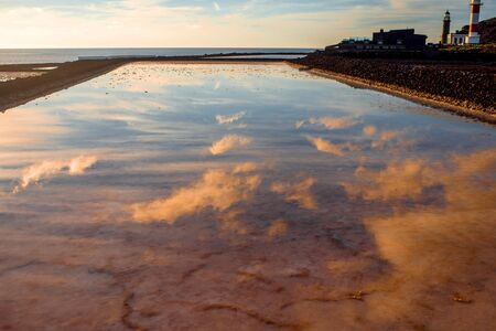 salt water: Volcanic pool on the salt manufaturing with pink salt water and sky reflection on La Palma island Stock Photo