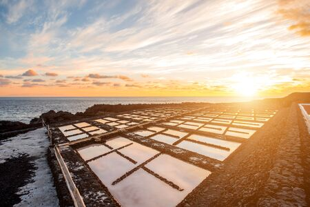 salt water: Volcanic pool on the salt manufaturing with pink salt water and sky reflection on the sunset on La Palma island