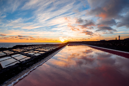 Volcanic pool on the salt manufaturing with pink salt water and sky reflection on the sunset on La Palma island