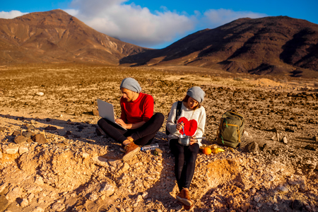 snack food: Young couple travelers working with laptop and having small picnic on the desert mountain landscape on Fuerteventura island in Spain