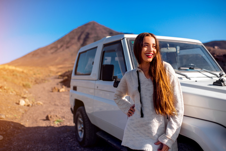 Young pretty woman dressed in sweater standing near the white jeep on the deserted and rocky landscape background Stock Photo