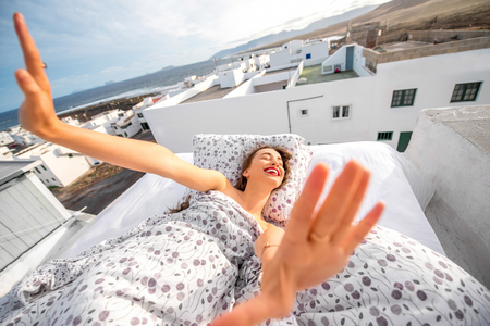 Mujer joven y linda que estira y que bosteza acostado en la cama en la azotea con casas blancas en el fondo.