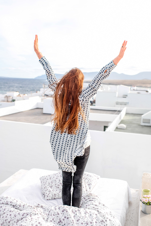 woman hands up: Young and cute woman raised hands sanding on the bed on the roof top with white houses on the background.