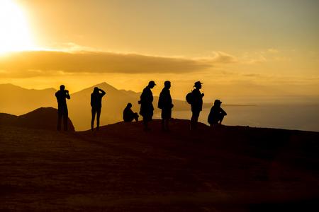 iluminado a contraluz: Silueta de la gente en la montaña con vista hermosa en la playa de Cofete, en la isla de Fuerteventura en la puesta de sol en España