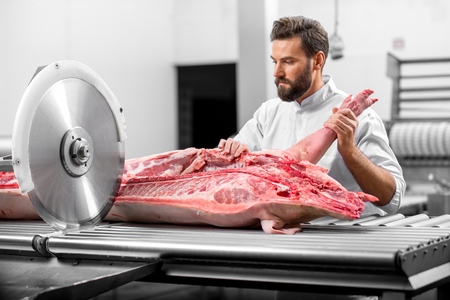 Handsome butcher cutting pork carcasse with big electric saw at the meat manufacturing