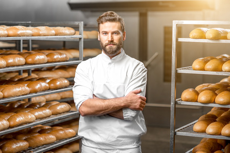 Portrait of handsome baker at the bakery with breads and oven on the background 版權商用圖片 - 54120271