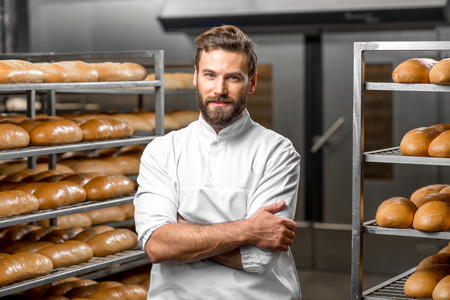 Portrait of handsome baker at the bakery with breads and oven on the background Foto de archivo