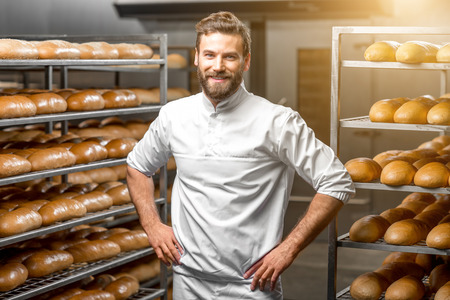 Portrait of handsome baker at the bakery with breads and oven on the background Stok Fotoğraf