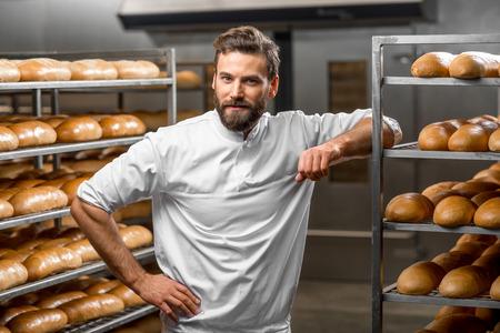 tranches de pain: Portrait de beau boulanger à la boulangerie avec du pain et du four sur le fond