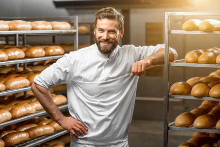 Portrait of handsome baker at the bakery with breads and oven on the background Stock Photo