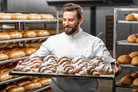 croissant: Handsome baker in uniform holding tray full of freshly baked croissants at the manufacturing Stock Photo