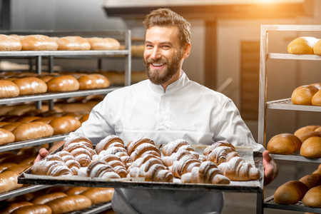 Handsome baker in uniform holding tray full of freshly baked croissants at the manufacturing Stockfoto