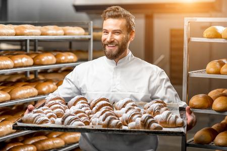 charolas: panadero hermoso en la bandeja de retención uniforme completo de croissants recién horneados en la fabricación