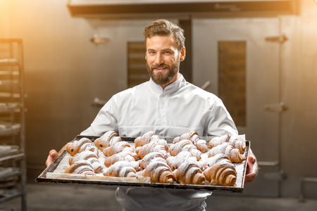 Handsome baker in uniform holding tray full of freshly baked croisants at the manufacturing