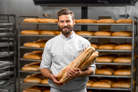 handsome  portrait: Handsome baker in uniform holding baguettes with bread shelves on the background at the manufacturing