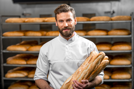 Handsome baker in uniform holding baguettes with bread shelves on the background at the manufacturing