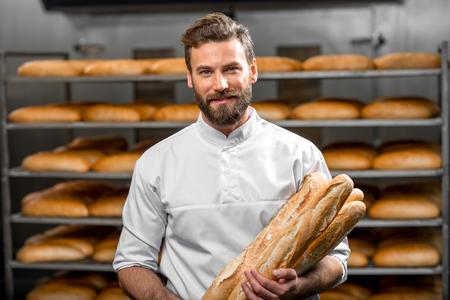 panadero: panadero hermoso en el uniforme que sostiene baguettes con estantes de pan en el fondo en la fabricación