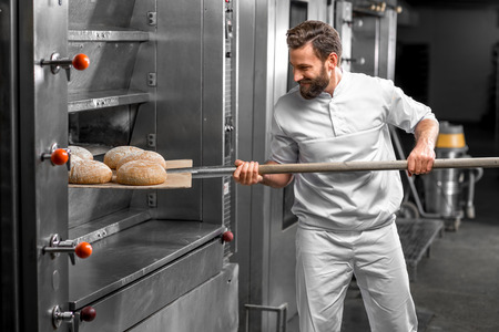 Handsome baker in uniform taking out with shovel freshly baked buckweat bread from the oven at the manufacturing