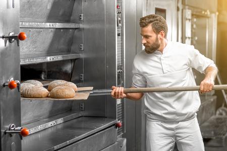 Knappe bakker in uniform nemen met schop vers gebakken boekweit brood uit de oven bij de vervaardiging Stockfoto - 54120231