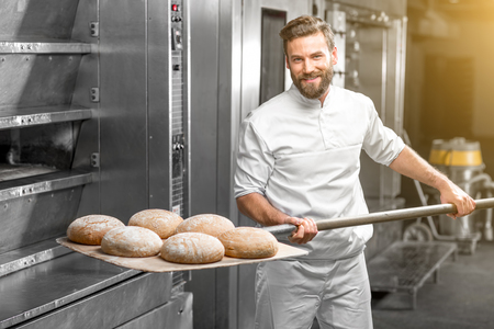 Handsome baker in uniform taking out with shovel freshly baked buckweat bread from the oven at the manufacturing Фото со стока - 54120233