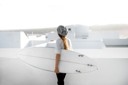 Young woman in white t-shirt and hat standing with surfboard on the roof top on the white city background. Stock Photo