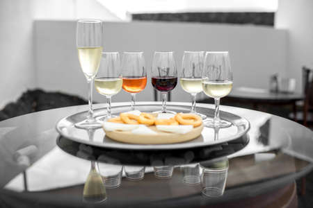 Set of six different wines in wineglasses with snack on the table for degustation