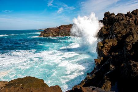 Volcanic Los Hervideros coastline with wavy ocean and blue sky on Lanzarote island in Spain Stock Photo