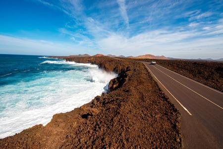 los hervideros: Volcanic Los Hervideros coastline with wavy ocean and road on Lanzarote island in Spain Stock Photo
