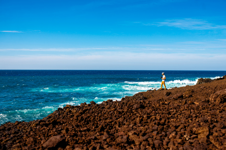 los hervideros: Male tourist photographing on the volcanic coast Los Hervideros on Lanzarote island in Spain