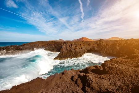 los hervideros: Los Hervideros rocky coast with wavy ocean and volcanos on the background on Lanzarote island in Spain