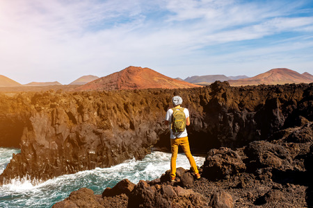 volcanos: Male tourist photographing Los Hervideros rocky coast with wavy ocean and volcanos on the background on Lanzarote island in Spain