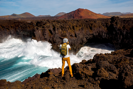 los hervideros: Male tourist photographing Los Hervideros rocky coast with wavy ocean and volcanos on the background on Lanzarote island in Spain