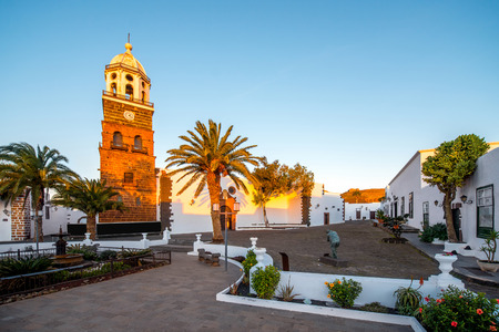 touristic: Central square with old church Nuestra Senora de Guadalupe in Teguise village on the sunset on lanzarote island