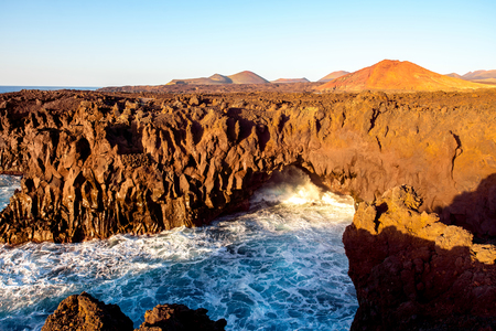 Los Hervideros rocky coast with wavy ocean and volcanos on the background on the sunset on Lanzarote island in Spain