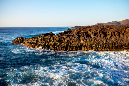 Los Hervideros rocky coast with wavy ocean on the background on the sunset on Lanzarote island in Spain