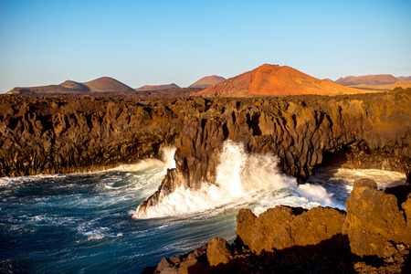 volcanos: Los Hervideros rocky coast with wavy ocean and volcanos on the background on the sunset on Lanzarote island in Spain